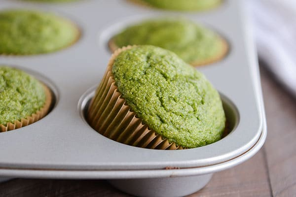baked green muffins in a muffin tin with one muffin tipping out of one of the slots