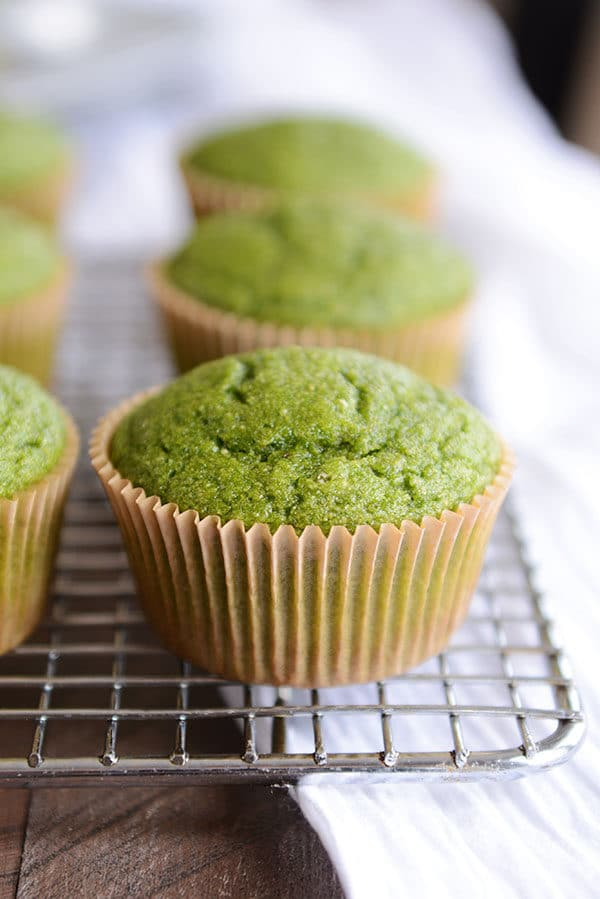 green muffins in brown muffin liners on a cooling rack