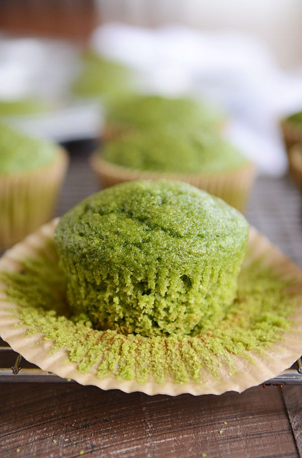 a green muffin on a cooling rack with the liner peeled off