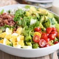 Grilled chicken cobb salad in white bowl with lettuce, tomatoes, eggs, bacon and blue cheese.
