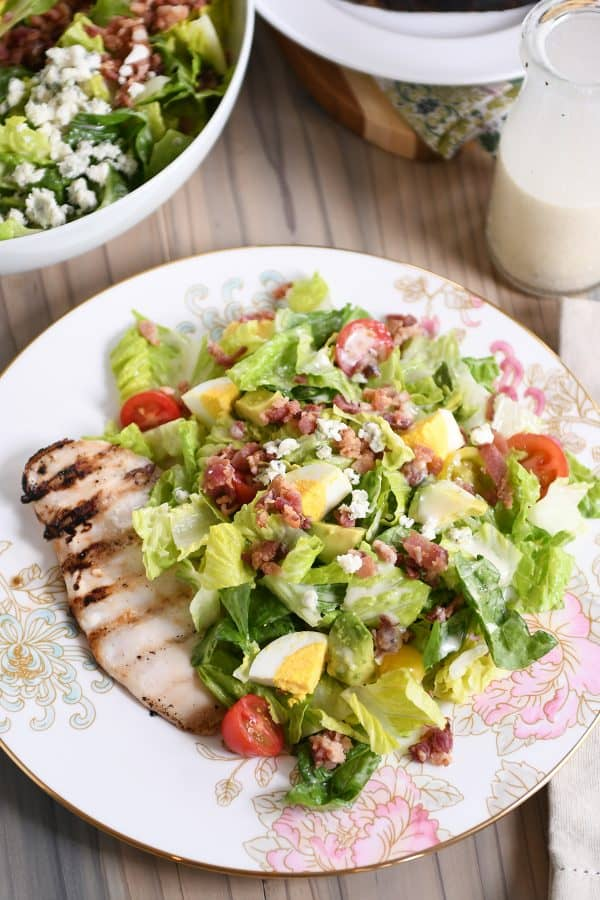 Grilled chicken cobb salad on white plate with pink flowers.