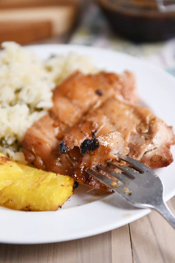 Grilled hawaiian chicken on plate with grilled pineapple and rice.