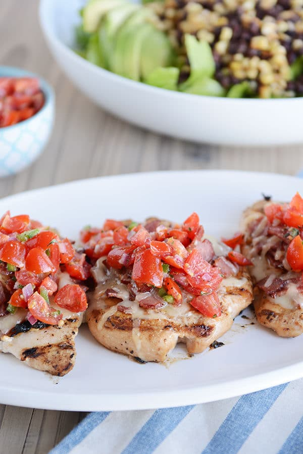 Three grilled chicken breasts with chopped tomatoes on top, and a salad with black beans and corn in the background.