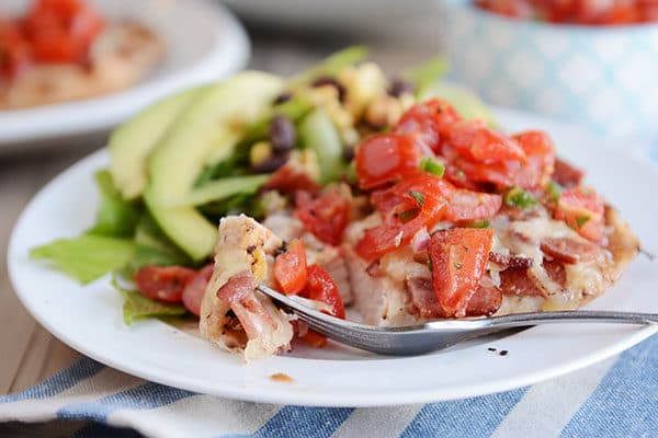 A plate with a grilled chicken breast and chopped tomatoes on top, and a green salad on the side.
