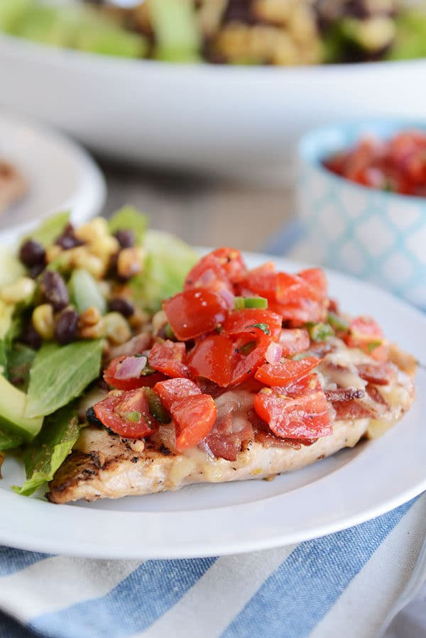 A grilled chicken breast topped with sliced tomatoes, and a green salad on the side, all on a white plate.