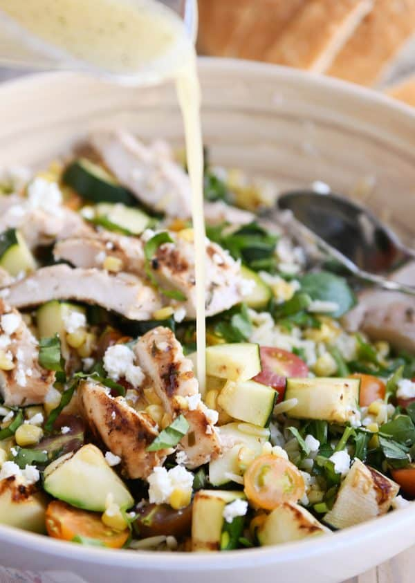 Honey lime dressing being poured onto grilled chicken orzo salad.