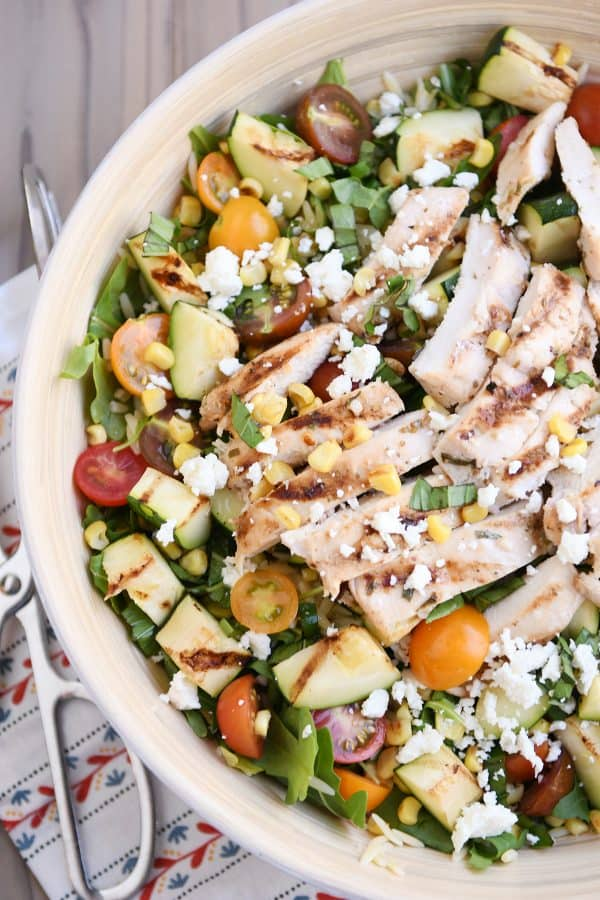 Top down view of grilled chicken orzo salad in white serving bowl.