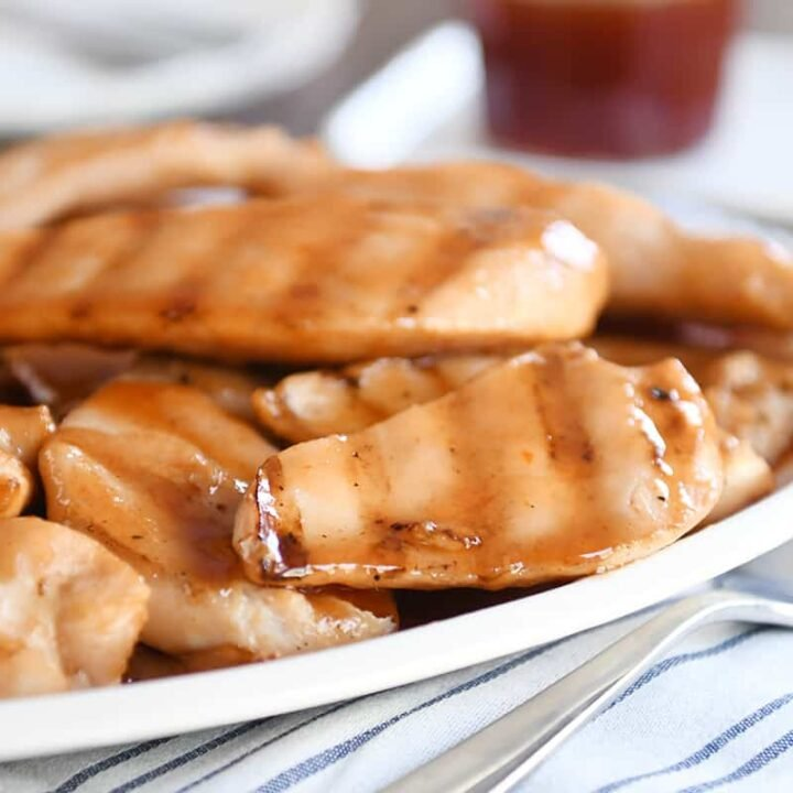 White platter of grilled sweet and sour chicken pieces.