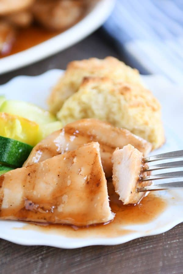 White plate with grilled sweet and sour chicken, zucchini and biscuits.