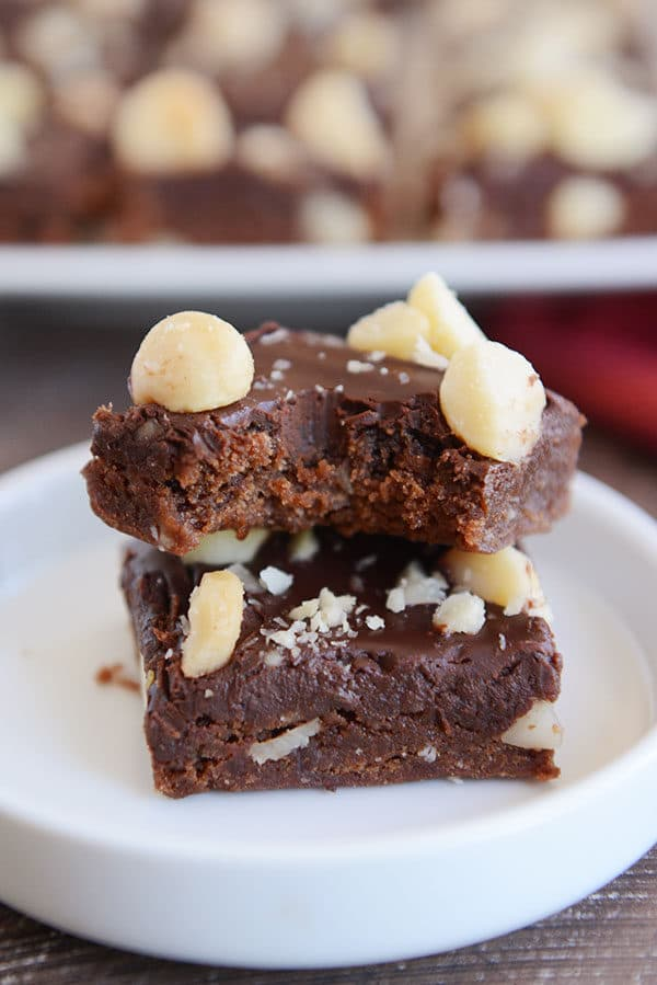 Two chocolate macadamia nut brownies stacked on top of each other with a bite taken out of the top one.