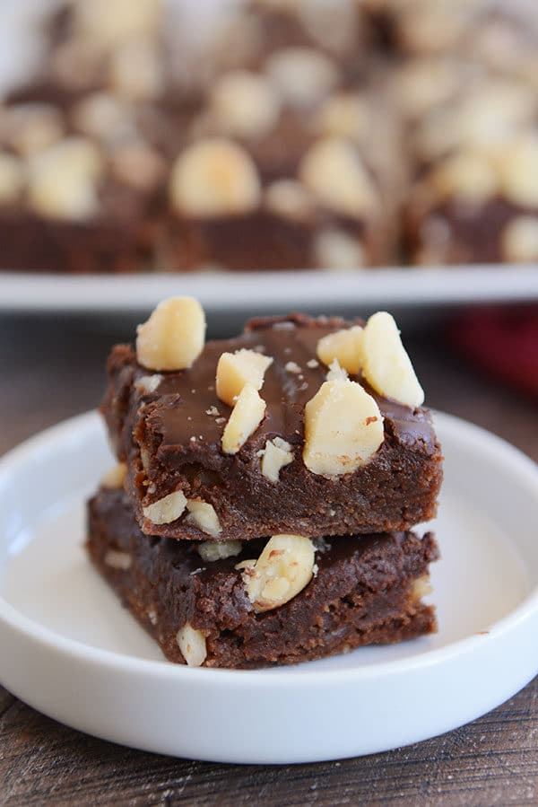 Two chocolate macadamia brownies stacked on top of each other inside a small white ramekin.