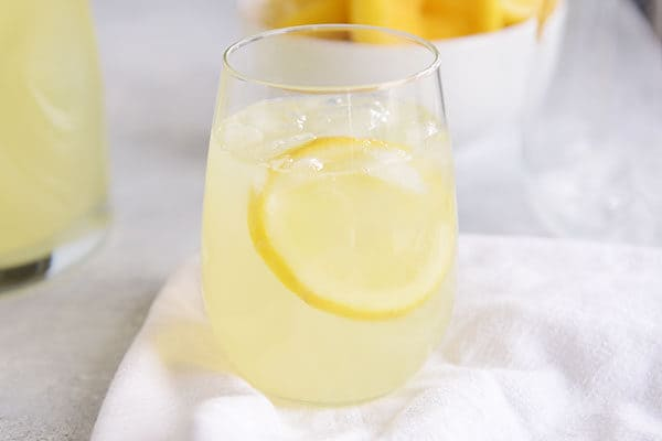 A glass of lemonade with ice and a slice of lemon in it.