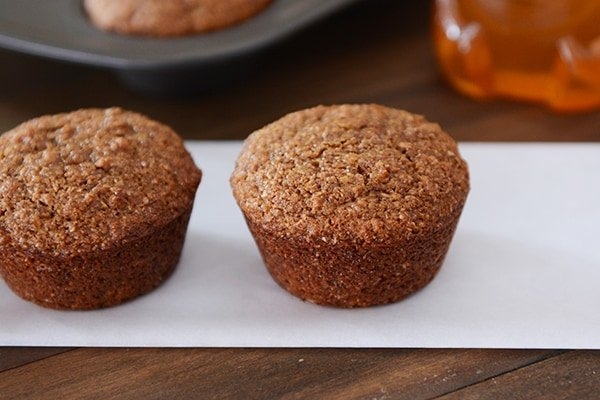 Two golden brown muffins side-by-side.