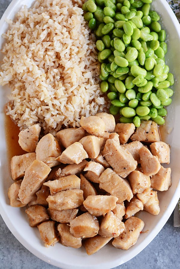 A large white oval platter with cooked chicken, lima beans, and cooked brown rice.