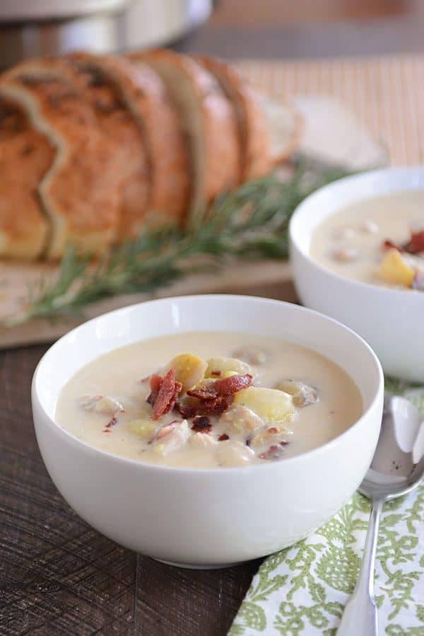 Two bowls of potato soup, topped with crumbled bacon, with fresh sage and a loaf of bread in the background.