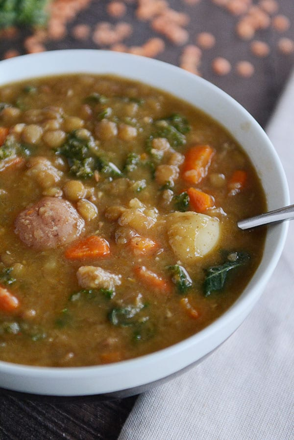 A bowl of soup filled with cooked lentils, carrots, sausage, potato, and spinach.