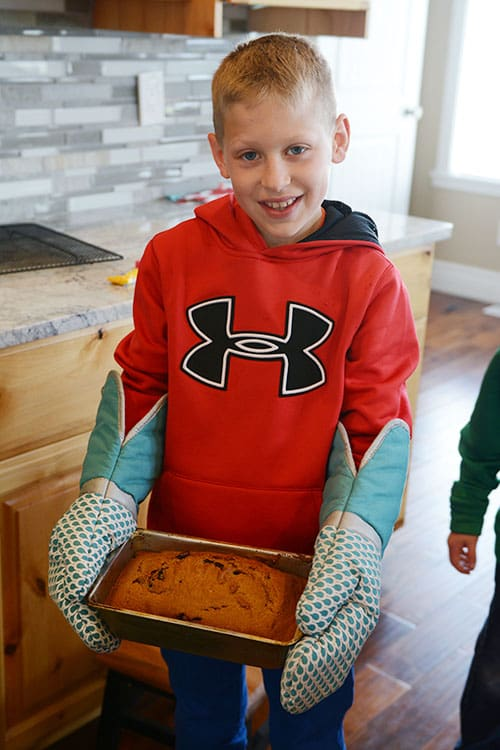 A little boy holding a cooked loaf of bread.