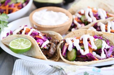 Korean beef tacos with slaw and sauce on white platter.