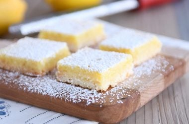 Lemon bars on cutting board sprinkled with powdered sugar.