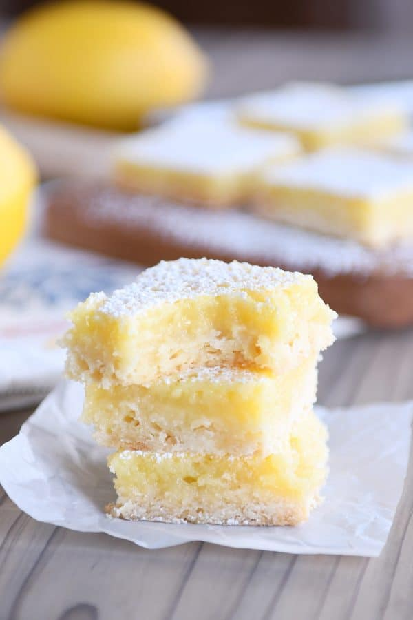 The best lemon bars stacked on each other and bite taken out of top lemon bar.