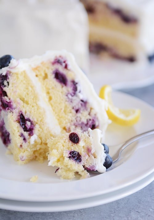 A big slice of lemon blueberry cake on a plate with blueberries and lemon on the side and the rest of the cake in the background.