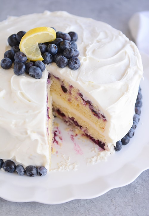 A two layer frosted lemon blueberry cake with a big piece cut out and blueberries and a lemon slice on top.