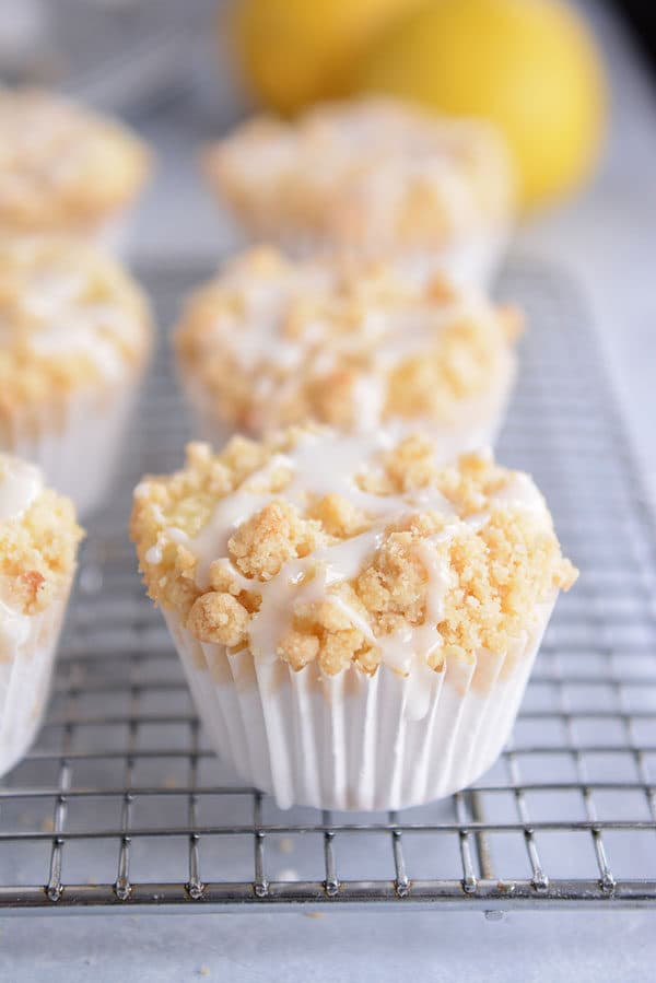 Streusel-topped lemon muffins with a drizzle of frosting on each one.