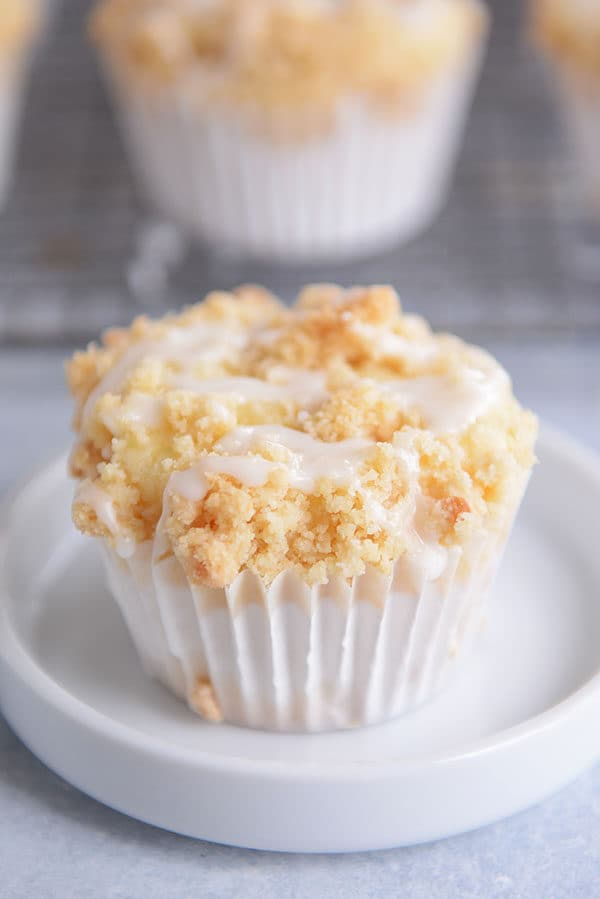 A streusel and frosting topped lemon muffin in a white liner.