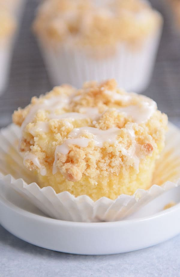 An unwrapped lemon crumb muffin with a drizzle of frosting on top.
