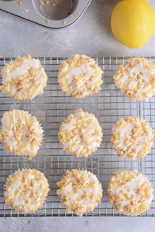 Top view of nine frosting drizzled lemon crumb muffins on a cooling rack.