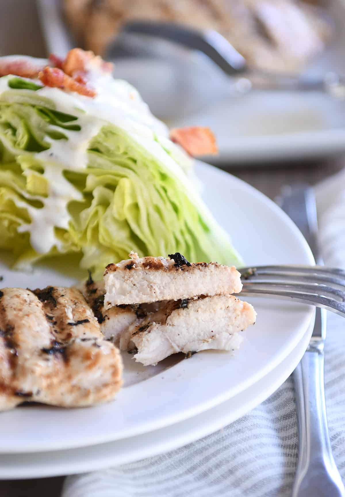 Lemon garlic grilled chicken cut into pieces on white plate.