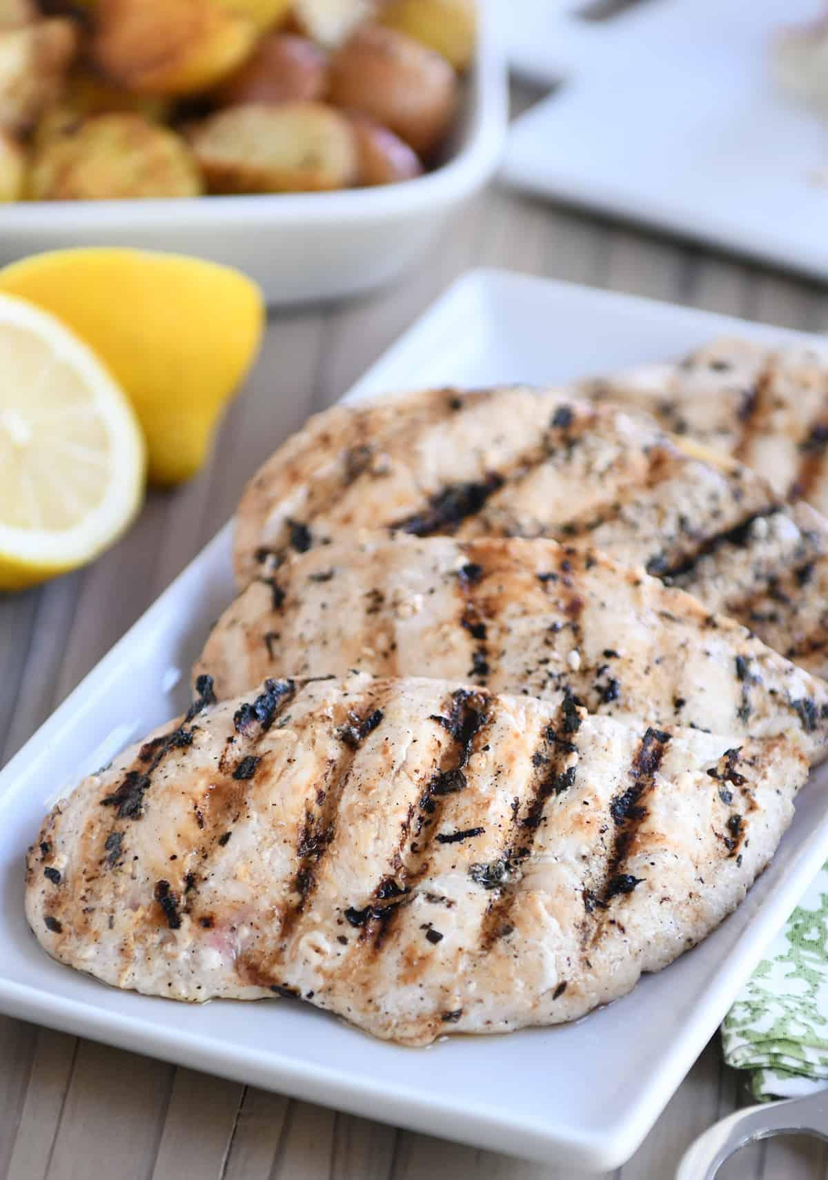 Several lemon garlic grilled chicken breasts on white platter.