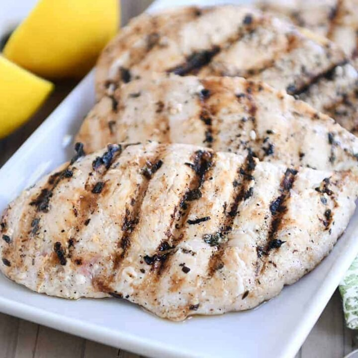 Several lemon garlic grilled chicken breasts on white platter.