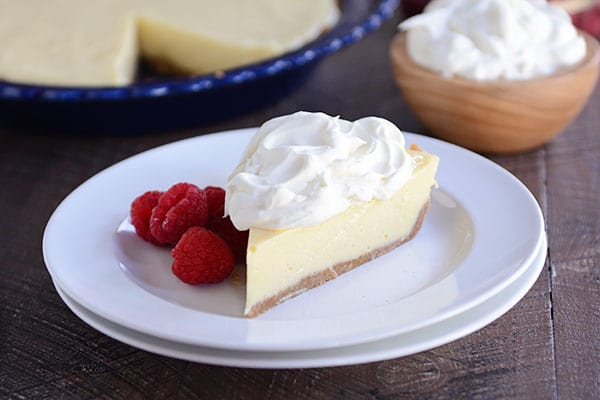 A slice of lemon pie with whipped cream on the top and raspberries on the side on a white plate, with the rest of a pie in a blue pie plate in the background.