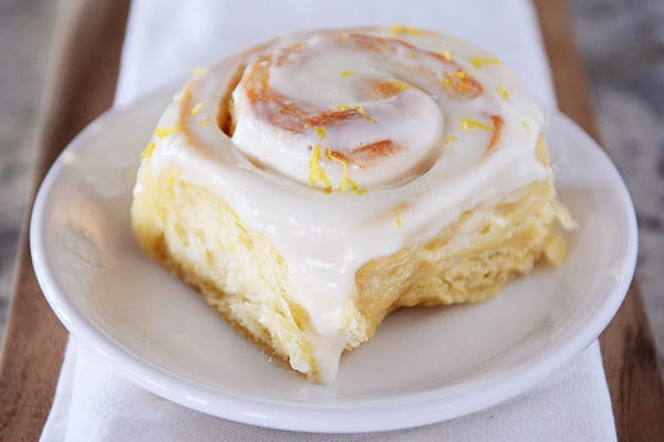 whole frosted lemon sticky bun on white plate