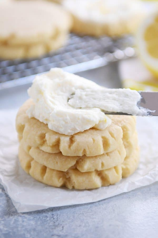 Stack of three lemon swig sugar cookies with pile of frosting on top.