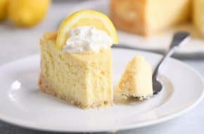 Slice of lemon white chocolate cheesecake on white plate.