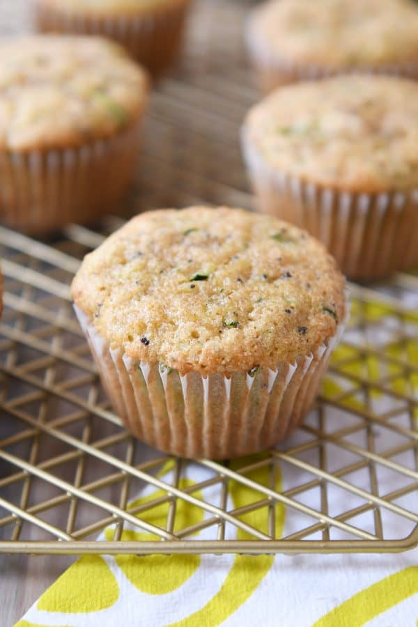Lemon poppy seed zucchini muffins on wire cooling rack.