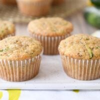 Several lemon poppy seed zucchini muffins on white plate.