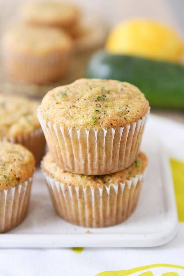 Two lemon zucchini poppy seed muffins stacked on each other.