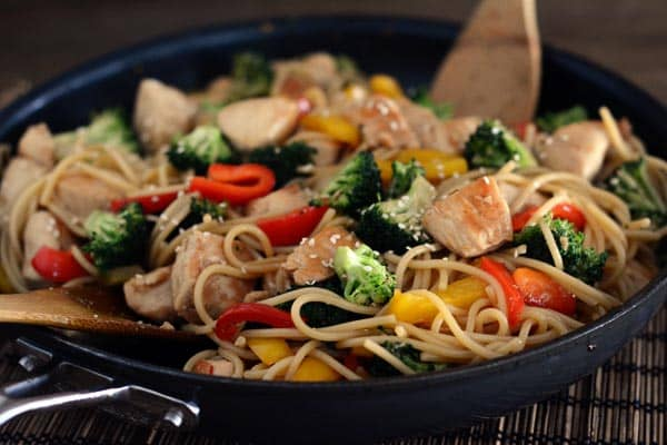 A cast iron skillet full of a lo mein, vegetable, and chicken stir fry.
