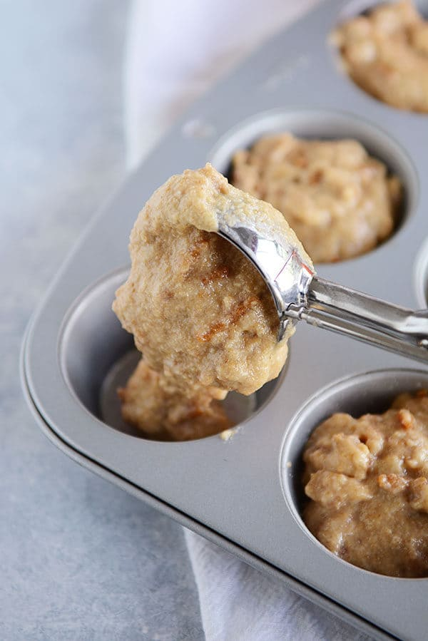 A muffin tin full of bran muffin batter, with an ice cream scoop filling the last slot in the muffin tin.