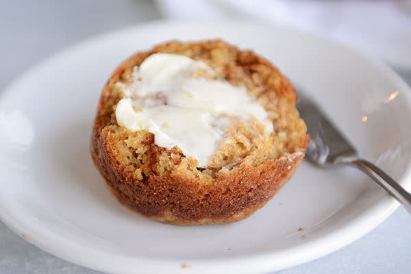 A half of a bran muffin on a white plate with butter spread on it.