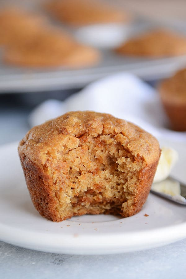 A cooked bran muffin with a bite taken out on a white plate and a pat of butter on a knife next to the muffin.