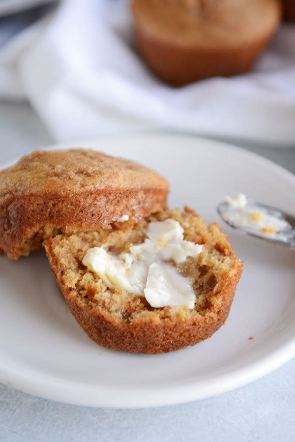 A bran muffin split in half with butter spread on it.