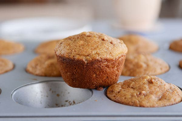 A muffin tin full of cooked bran muffins, with one muffin taken out and placed on top.