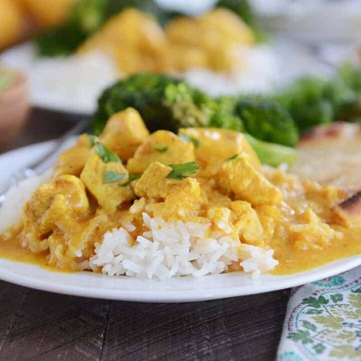 Thai chicken mango red curry sauce over white rice on white plate.
