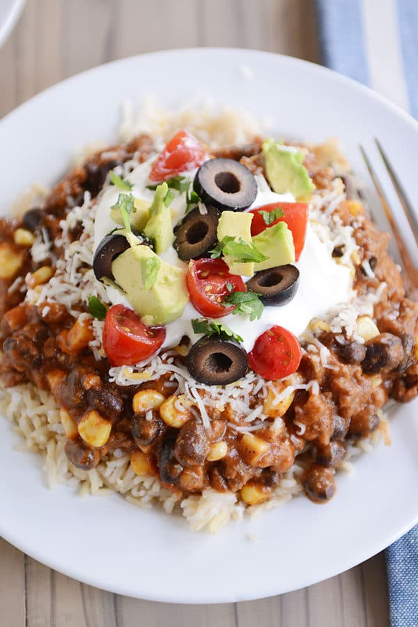 Top view of a white plate of cooked rice topped with a beef and corn mixture and taco toppings.