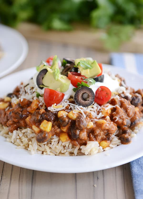 A white plate of cooked rice topped with a Mexican beef and corn mixture, tomato, olive, avocado, and sour cream.
