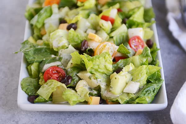 Chopped romaine salad with black beans, cubes of cheese, and cherry tomatoes sprinkled throughout.